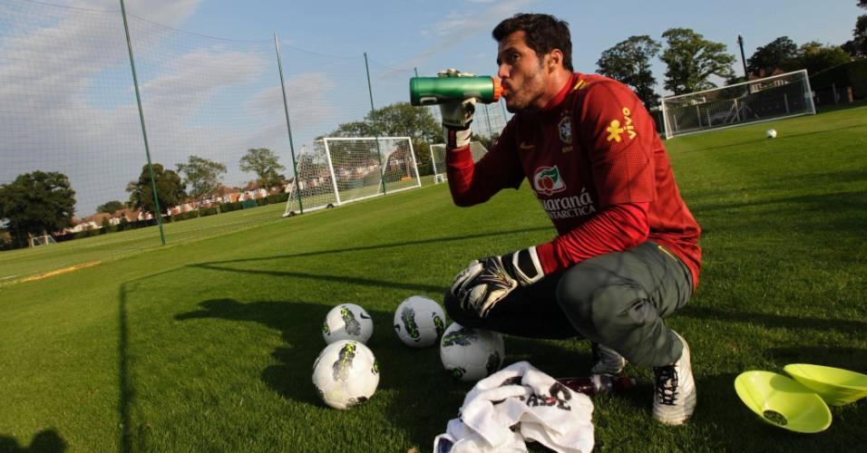 Goleiro Júlio César se refresca durante treino da seleção brasileira em Londres