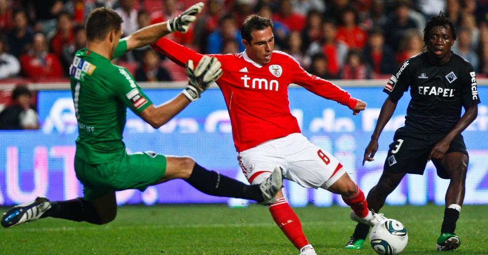 O meia Bruno Cesar, do Benfica,chuta a bola para fazer um gol sobre o goleiro francês Romuald Peiser, do Acadêmica, pelo Português