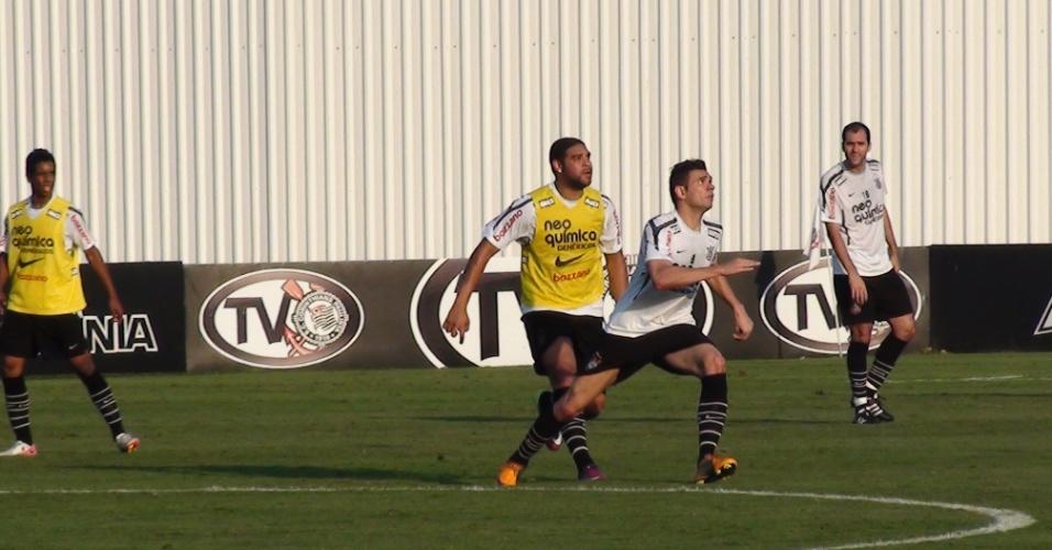Adriano e Leandro Castan olham para a bola e se preparam para pular em treino do Corinthians