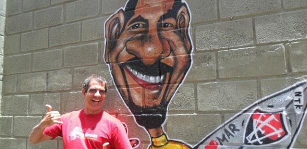 Durval Lelys, astro do Asa de Águia, posa ao lado de sua caricatura no Barradão