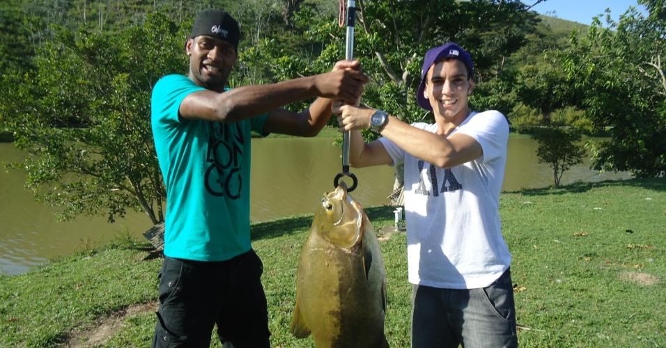 Dedé e Caio seguram peixe fisgado durante as férias