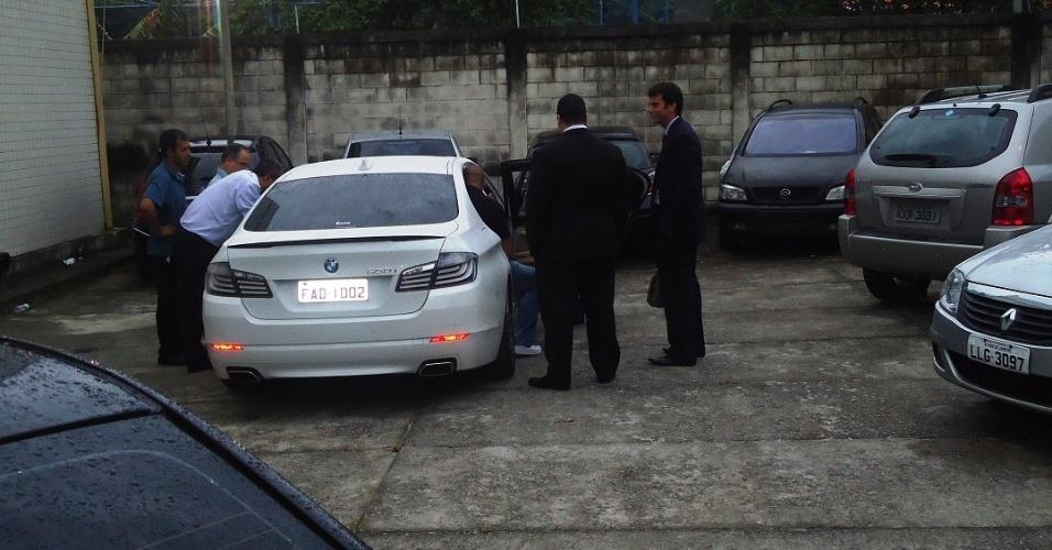 Adriano tem dificuldade para entrar no banco traseiro de seu carro durante perícia da polícia