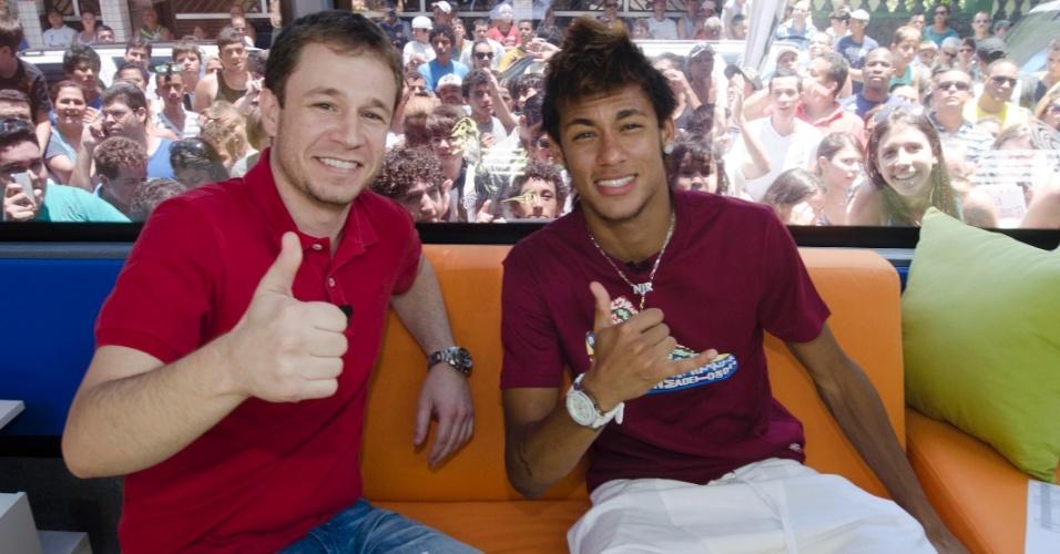 Tiago Leifert e Neymar acenam dentro do estúdio móvel do Globo Esporte, em Santos