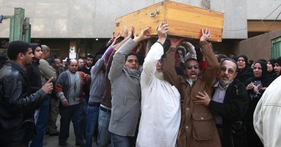 Pai e parentes carregam caixão de filho que morreu durante batalha em campo no Egito
