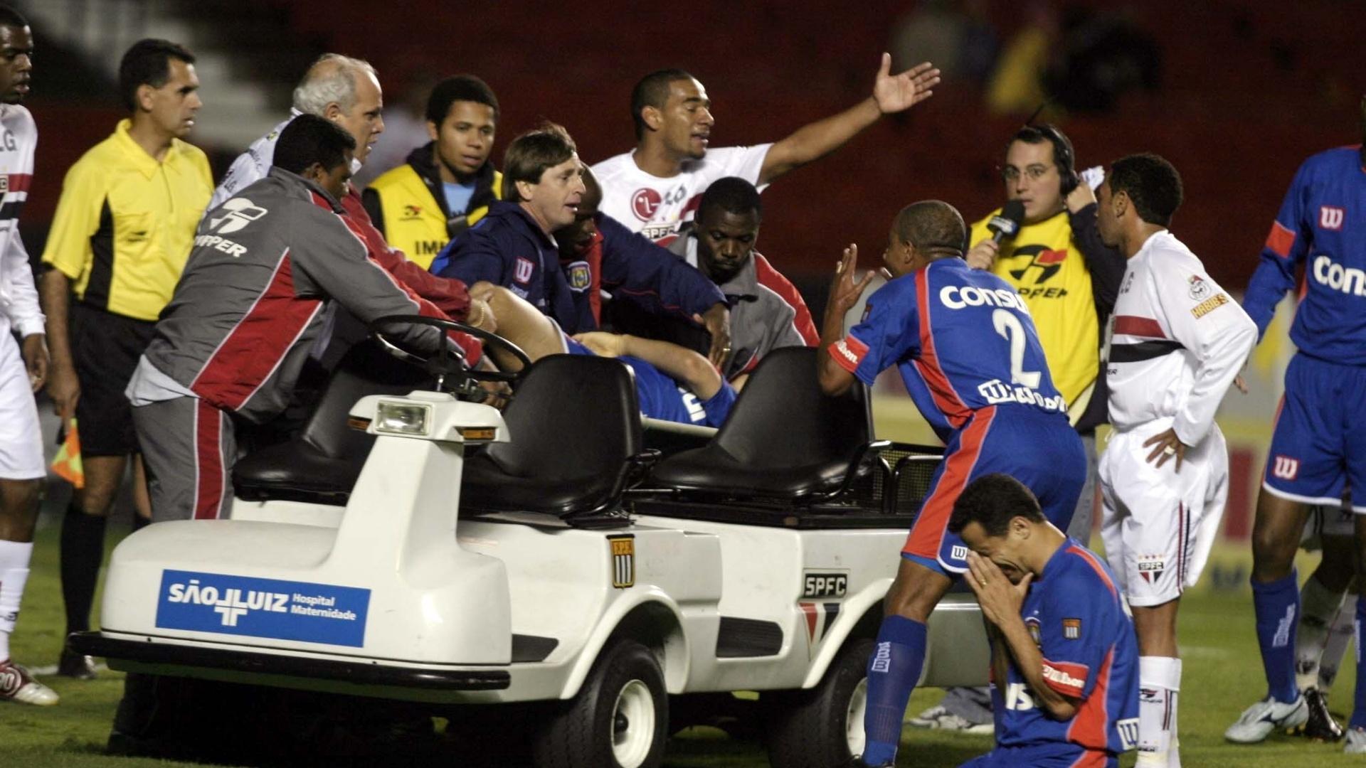 Jogadores de São Caetano e São Paulo se desesperam enquanto o corpo de Serginho é retirado de maca; zagueiro morreu em campo após sofrer um mal súbito (27/10/2004)