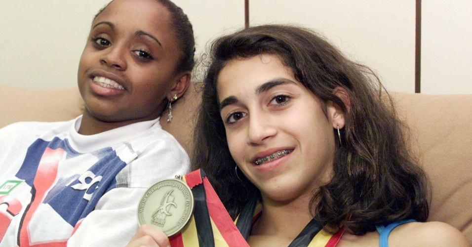 Ao lado de Daiane dos Santos, Daniele Hypolito mostra a medalha de ouro conquistada por ela no Mundial de ginástica de 2001