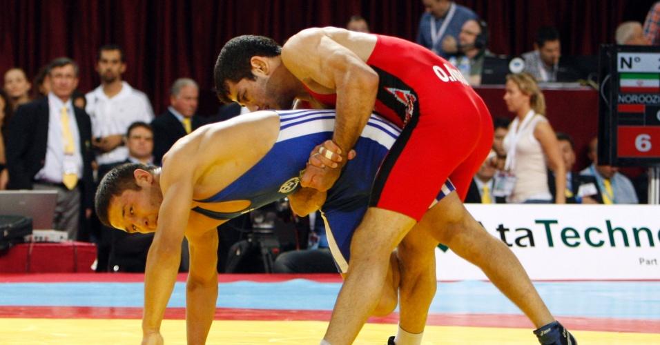O iraniano Omid Haji Noroozi (de vermelho) tenta aplicar um golpe em Almat Kebispayev, do Cazaquistão durante o Mundial de Luta Olímpica na Turquia (13/09/2011)