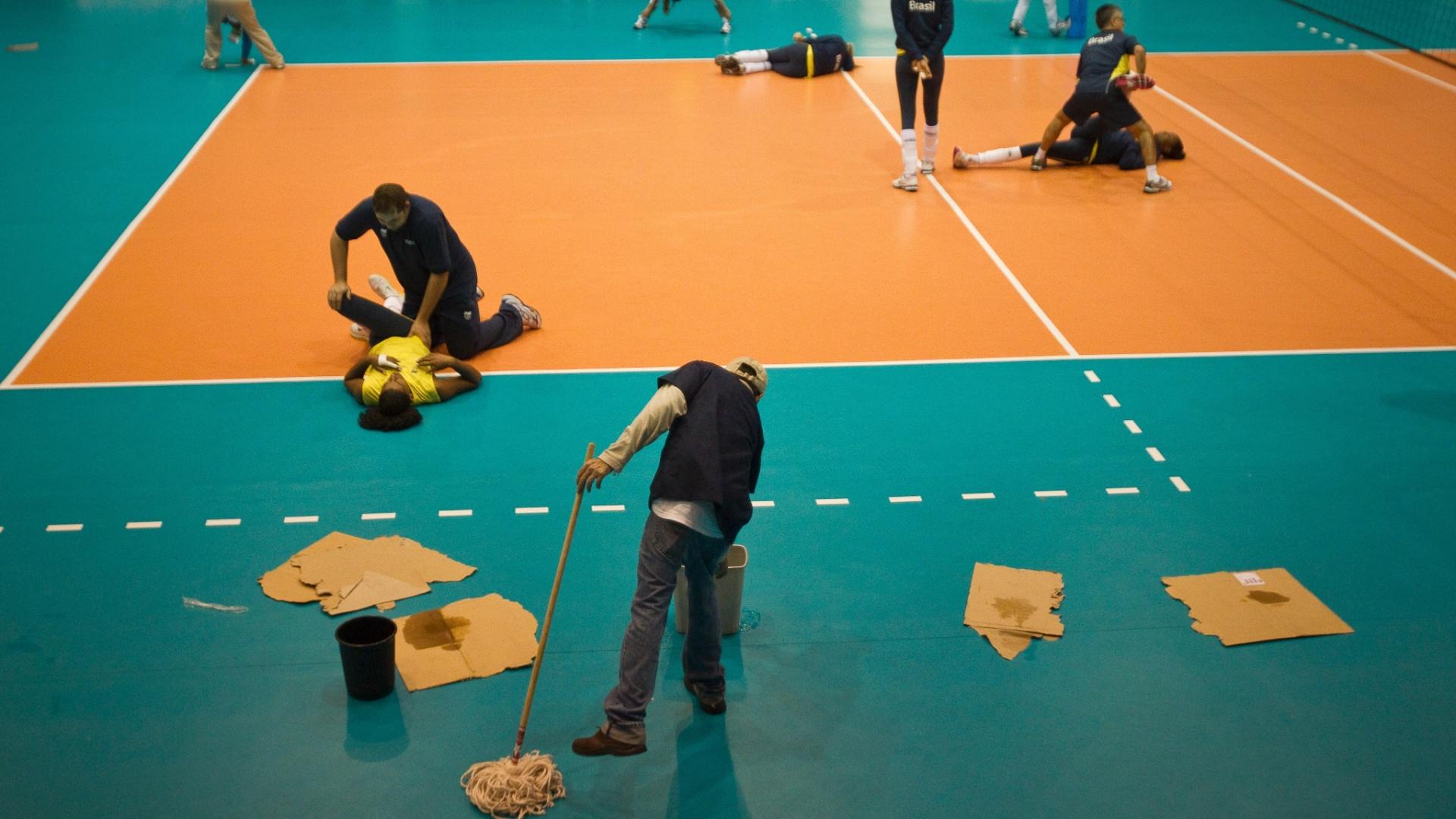 Brasileiras fazem alongamento enquanto a quadra de vôlei é seca devido à presença de goteiras no ginásio