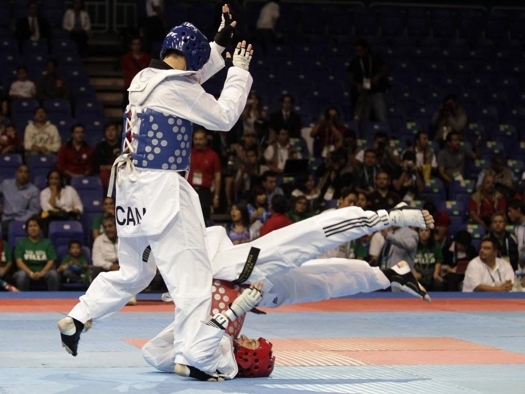 O canadense Jocelyn Addison acerta um golpe em Heiner Oviedo, da Costa Rica, que sofre uma queda feia na disputa do taekwondo para lutadores com até 58kg