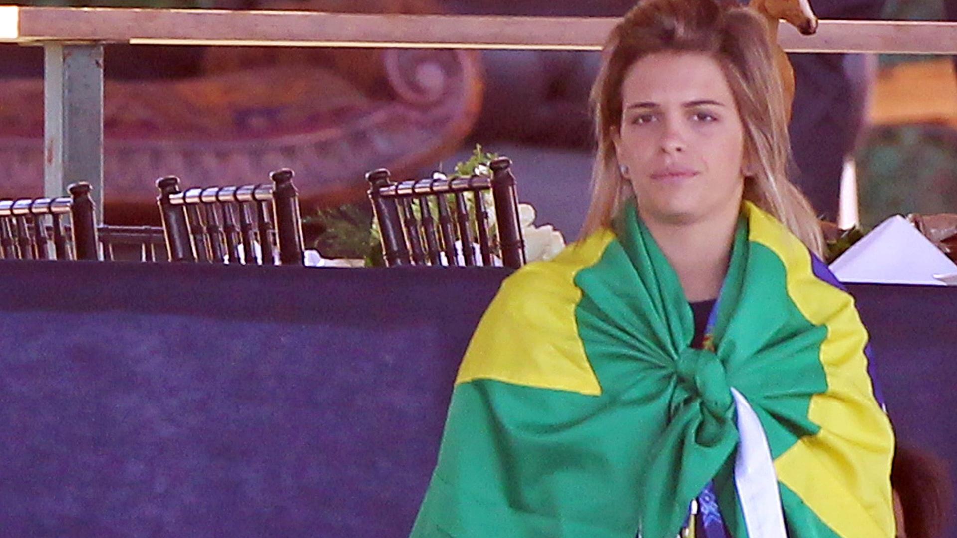 Amazona Luiza Almeida se enrola em bandeira brasileira antes de iniciar a prova de adestramento do hipismo (16/10/2011)