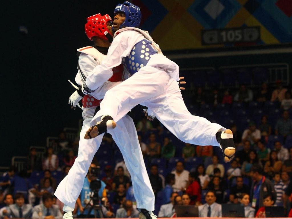 Diogo Silva (de azul) tenta acertar golpe no jamaicano Nicholos Dusard, na vitória por 8 a 5 no taekwondo (16/10/2011)