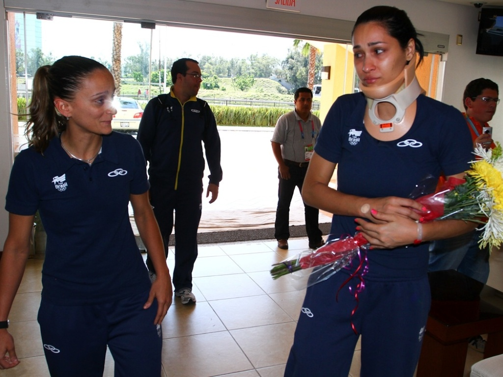 Jaqueline chega ao hotel da seleção de vôlei após deixar o hospital e encontra a líbero Fabi (16/10/2011)