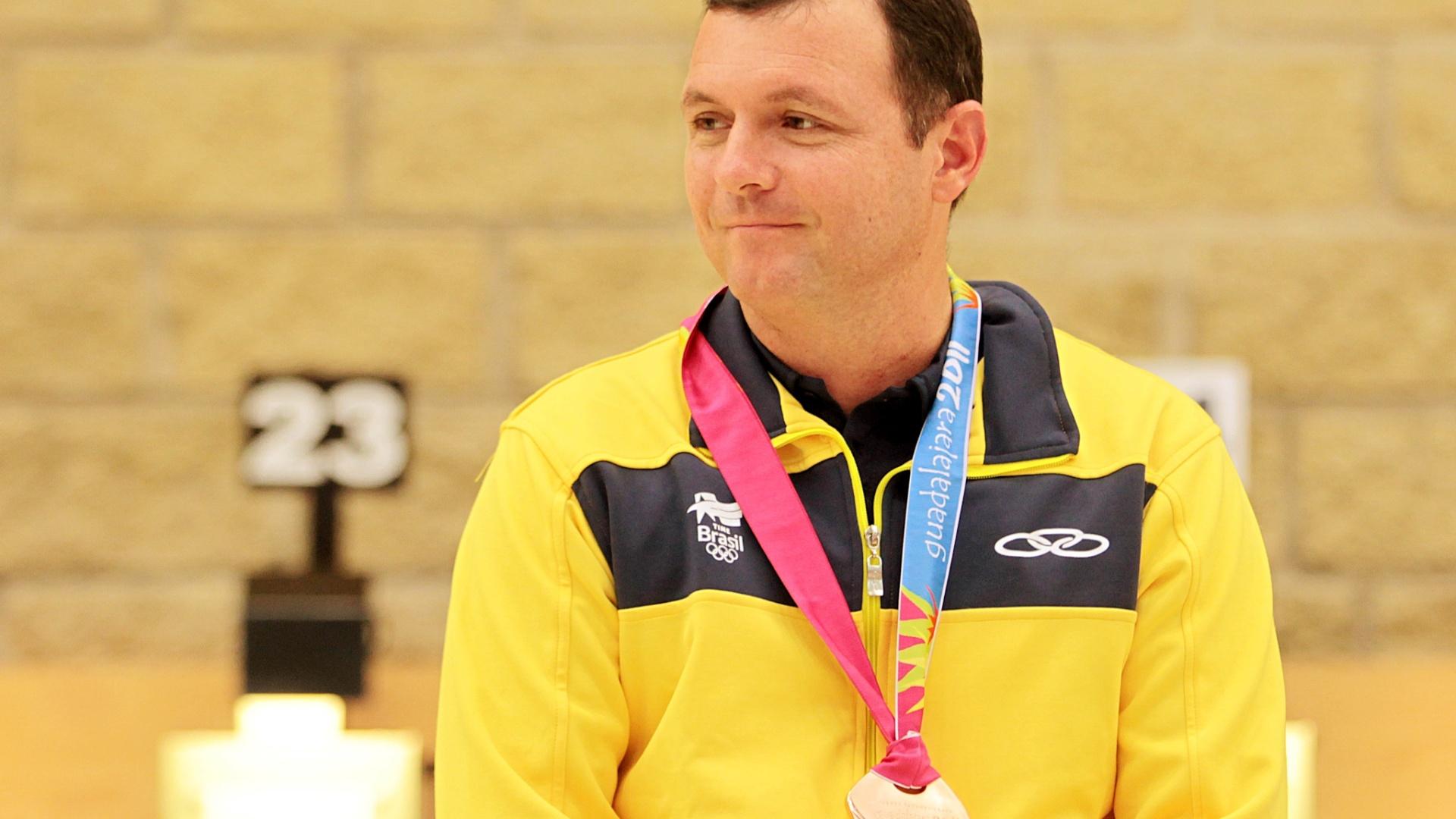 Julio Almeida não parece muito satisfeito ao receber a medalha de bronze no tiro esportivo