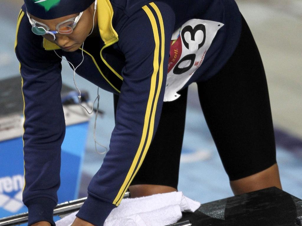 A nadadora brasileira Tatiane Sakemi, que se classificou para a final dos 100 m peito, seca o bloco de partida antes da prova (17/10/2011)