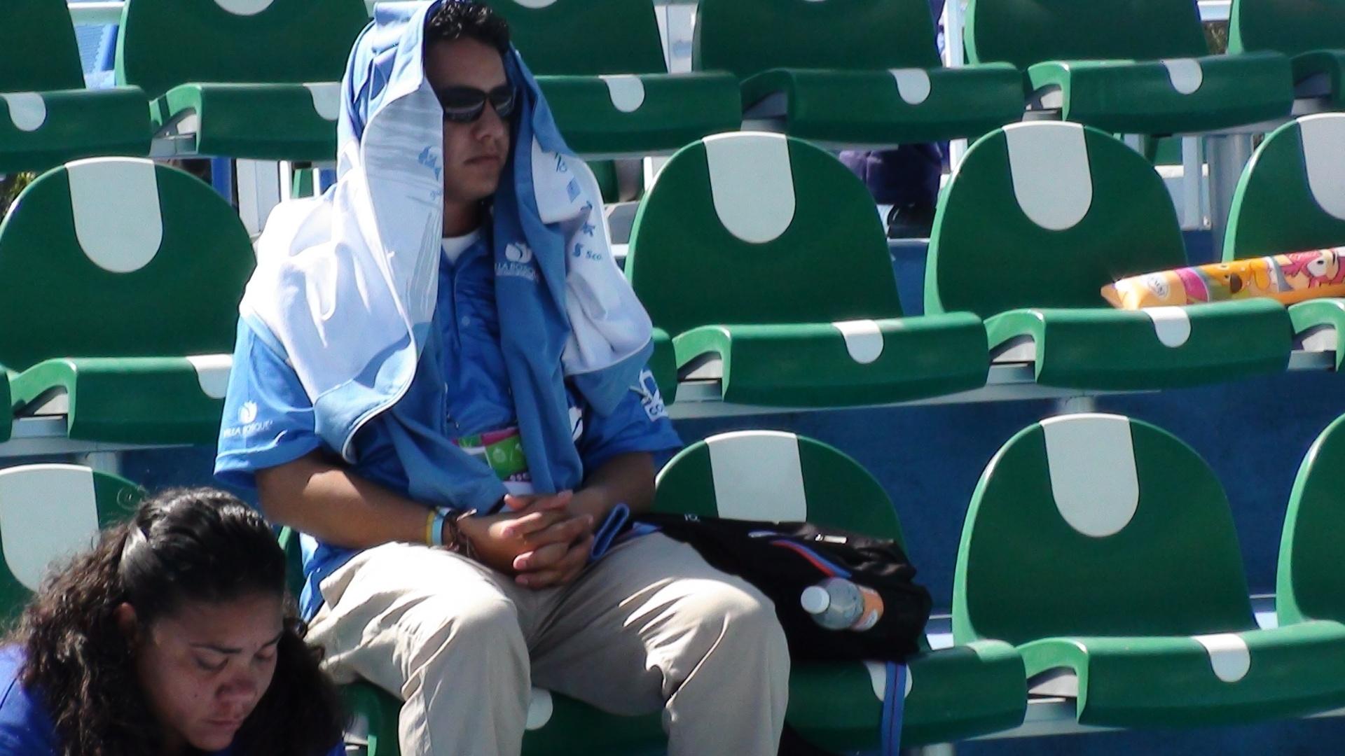 Espectador se protege do calor no complexo de tênis de Guadalajara durante jogo do Pan