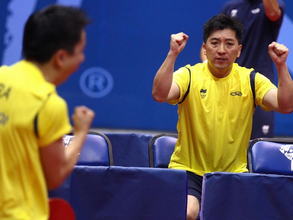 Hugo Hoyama comemora com Tsuboi a vitória na primeira partida da final contra a Argentina no tênis de mesa por equipes