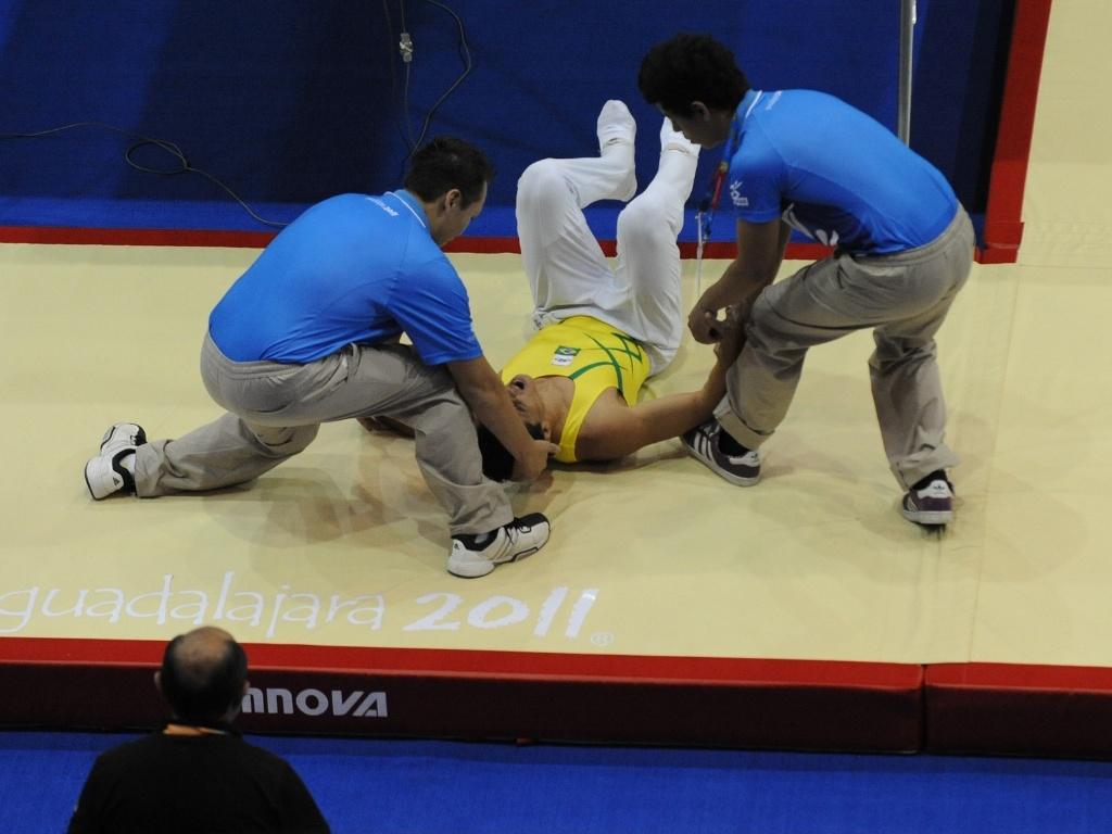 Brasileiro Carlos Ramirez Pala, da ginástica de trampolim, cai durante apresentação e sai carregado no Pan (18/10/2011)
