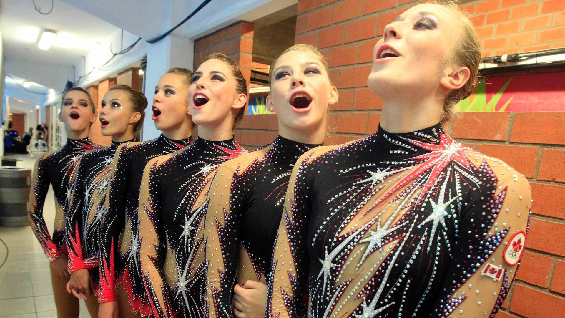 A equipe canadense de ginástica rítmica canta o hino do país enquanto o compatriota recebe o ouro no trampolim