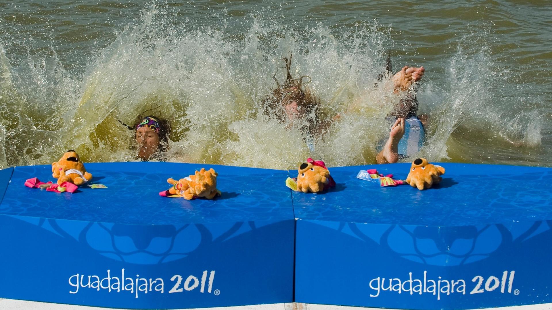 Remadoras argentinas mergulham na água após receberem medalha de ouro no pódio do Pan (19/10/2011)