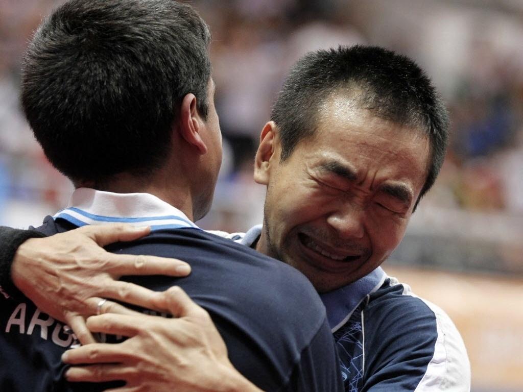Song Liu, da Argentina, chora com seu técnico após o ouro individual no tênis de mesa, nesta quinta (20/10/2011)