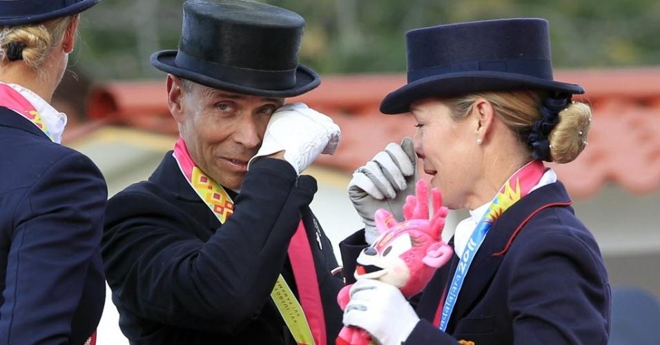 Norte-americanos Steffen Peters (e) e Marisa Festerling choram no pódio do adestramento no Pan
