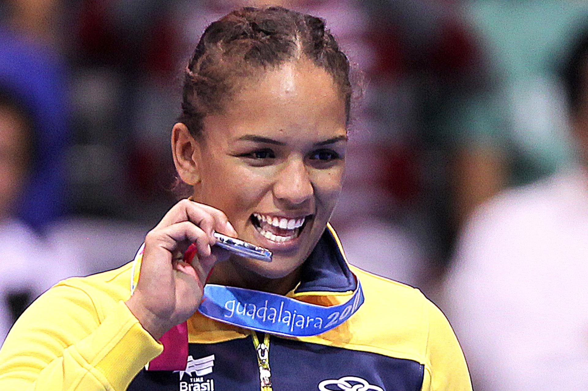Aline Ferreira morde a medalha prata conquistada na categoria até 72 kg da luta olímpica