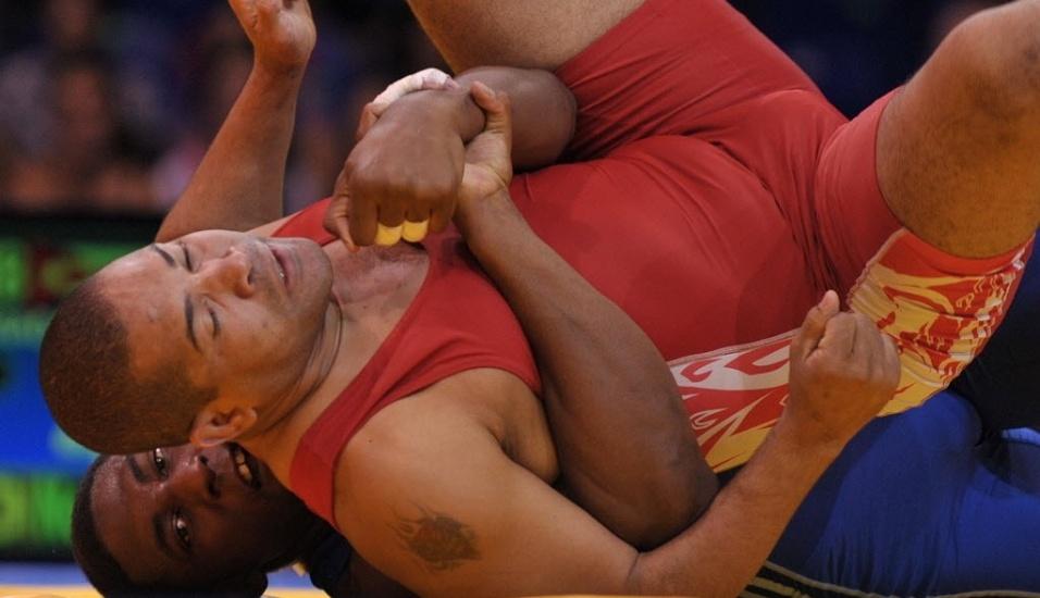 Lutador cubano Yunior Estrada exibe sua tatuagem com um