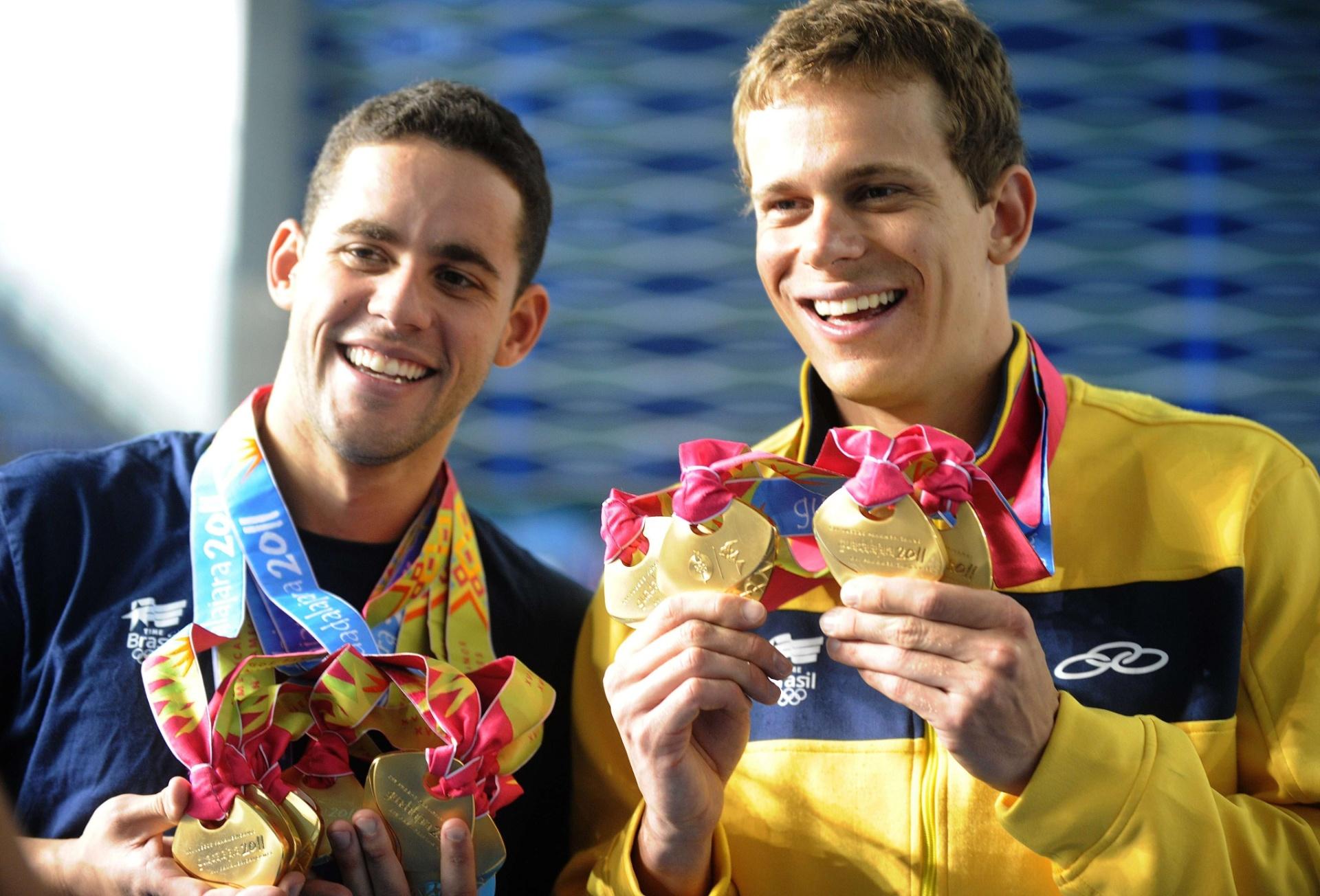 Thiago Pereira (e) e Cesar Cielo mostram as medalhas de ouro conquistadas por eles no Pan-2011