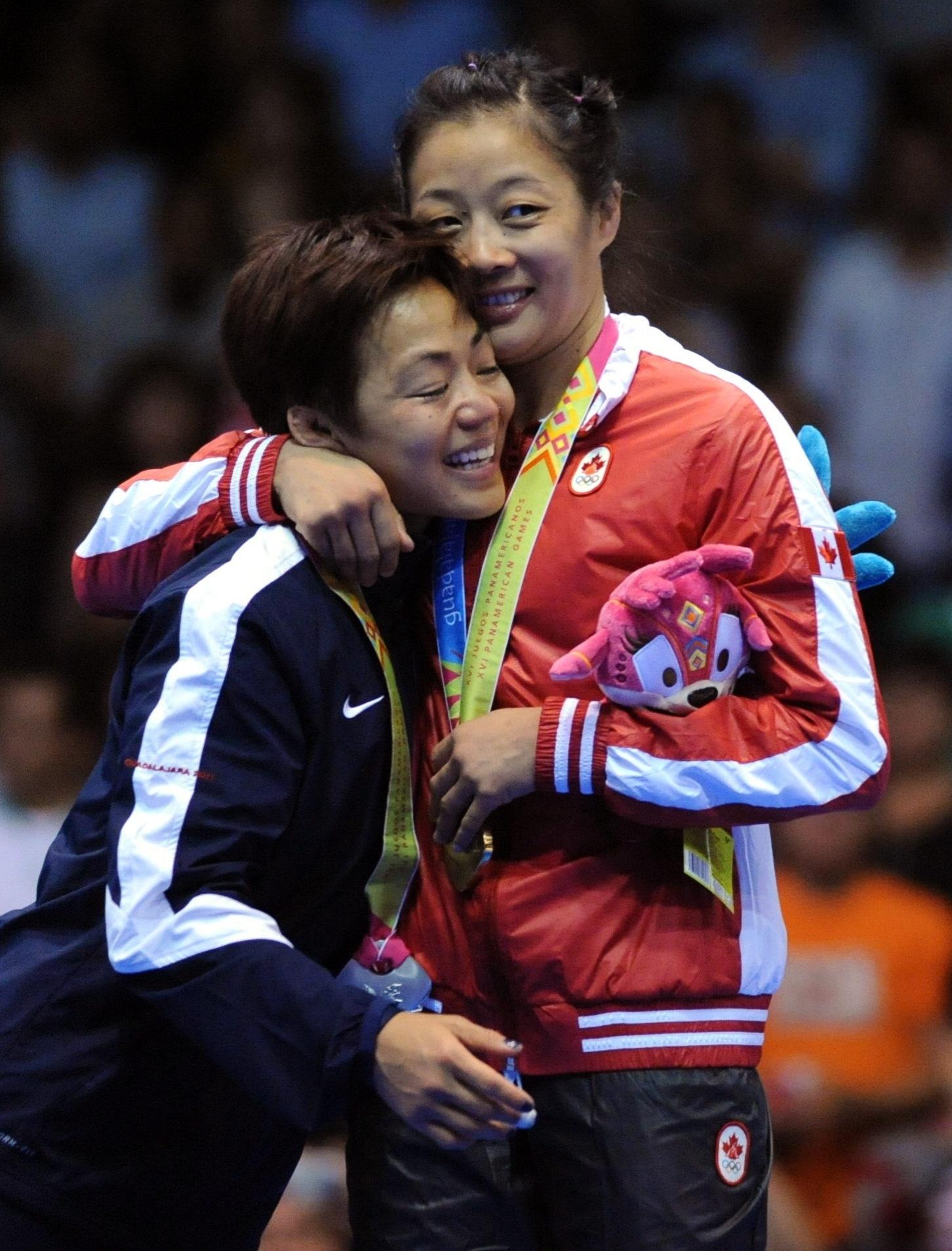 Carol Huyng e Clarissa Chun se confraternizam na cerimônia de premiação da luta olímpica, categoria até 48kg