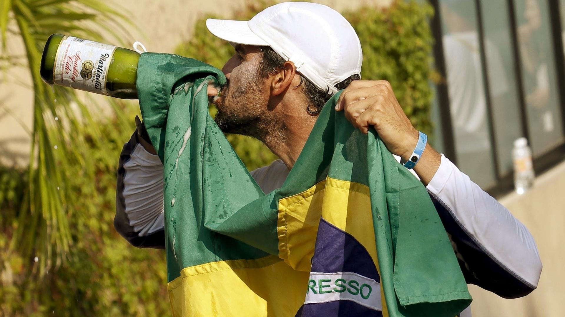 Ricardo Winicki, o Bimba, comemora bebendo champanhe depois de conquistar o ouro na classe RS:X da vela (23/10/2011)