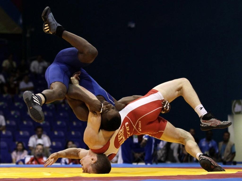 Cubano Yowlys Bonne, de azul, deixa Ryley Walker com o nariz no chão durante luta olímpica do Pan (24/10/2011)