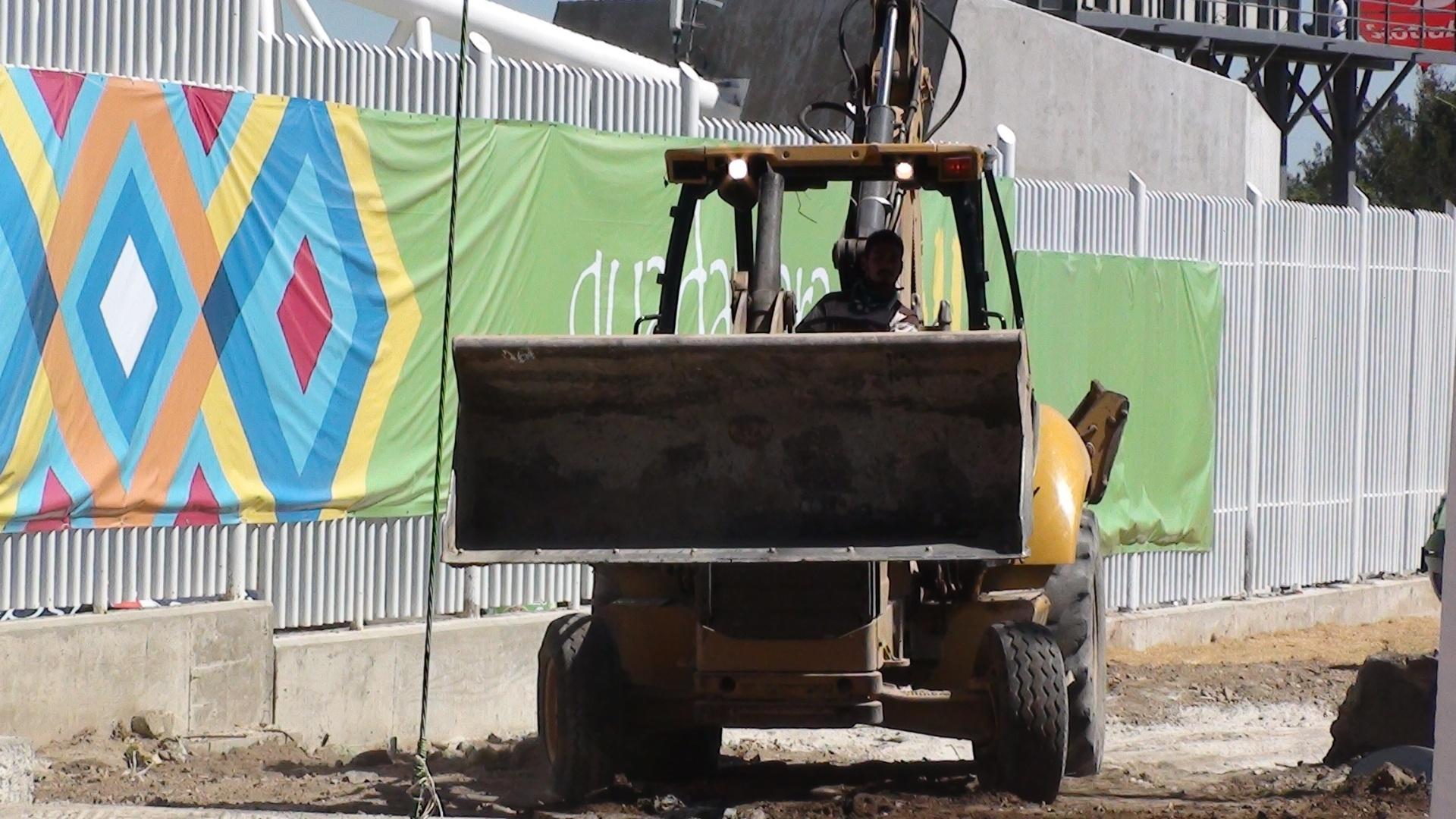 Trator trabalha no entorno do estádio que recebe provas de atletismo no Pan (24/10/2011)