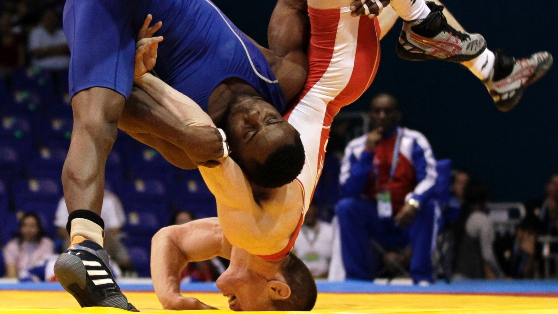 Yowlys Bonne (azul) de Cuba, e o canadense Ryley Walker, em combate da luta olímpica, categoria até 60 kg