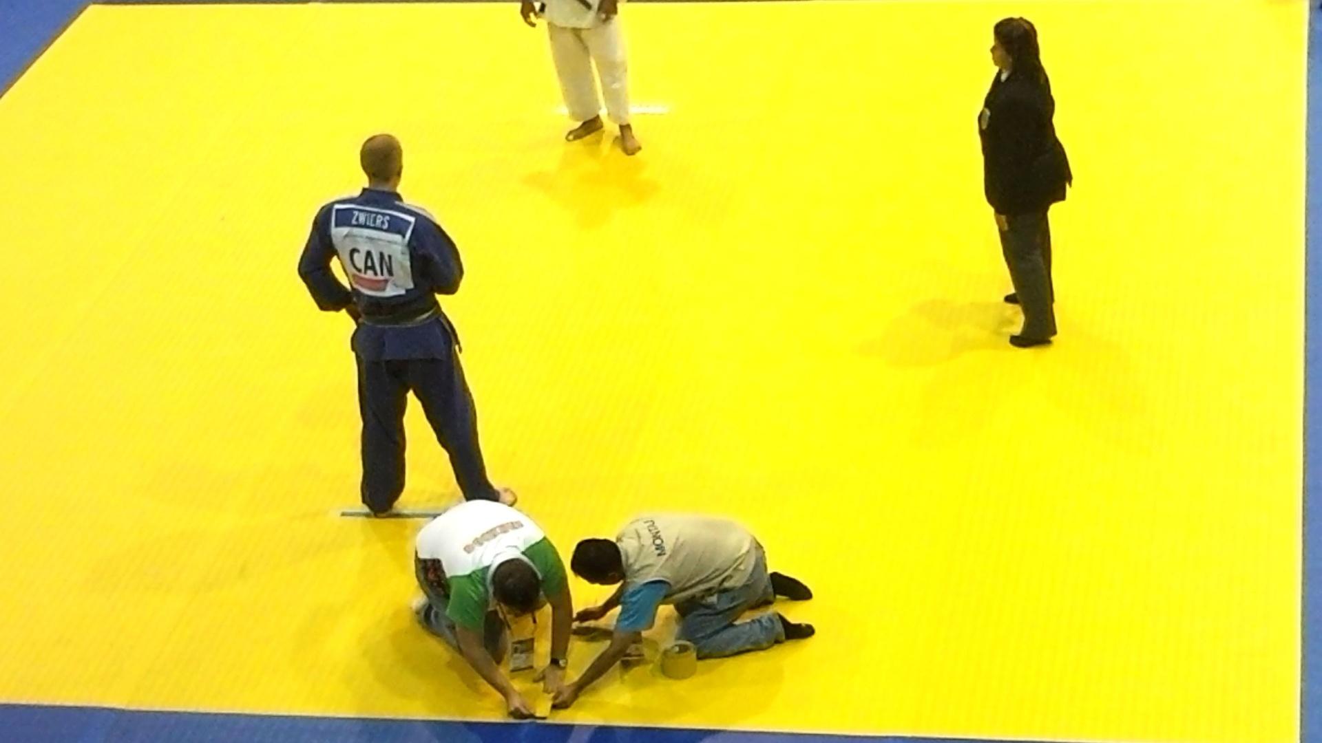 Funcionários fazem reparo no tatame danificado durante a luta entre o canadense Stefan Zwiers e o colombiano Camilo Castano no Pan (26/10/2011)