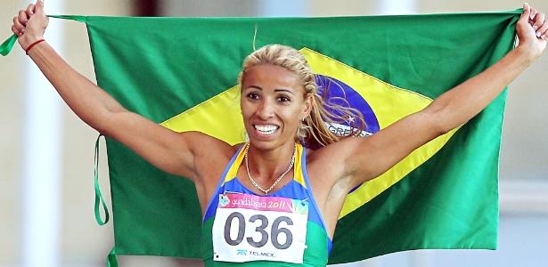Lucimara Silvestre comemora com a bandeira brasileira o seu ouro no heptatlo
