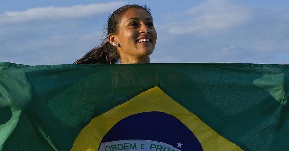 Ana Claudia Lemos sorri com a bandeira brasileira ao conquistar a medalha de ouro nos 200 m no Pan (27/10/2011)