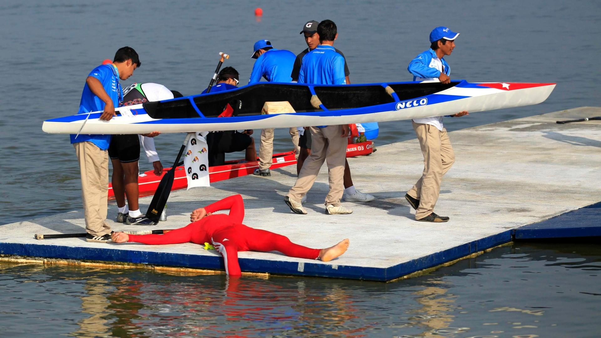 Após conquistar a prata na canoagem, o cubano Reydel Ramos descansa enquanto voluntários retiram sua canoa da água