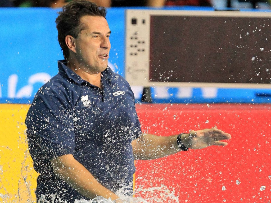 meninas do polo aquático brasileiro jogam o técnico Roberto Chappini na piscina para comemorar o bronze em Guadalajara