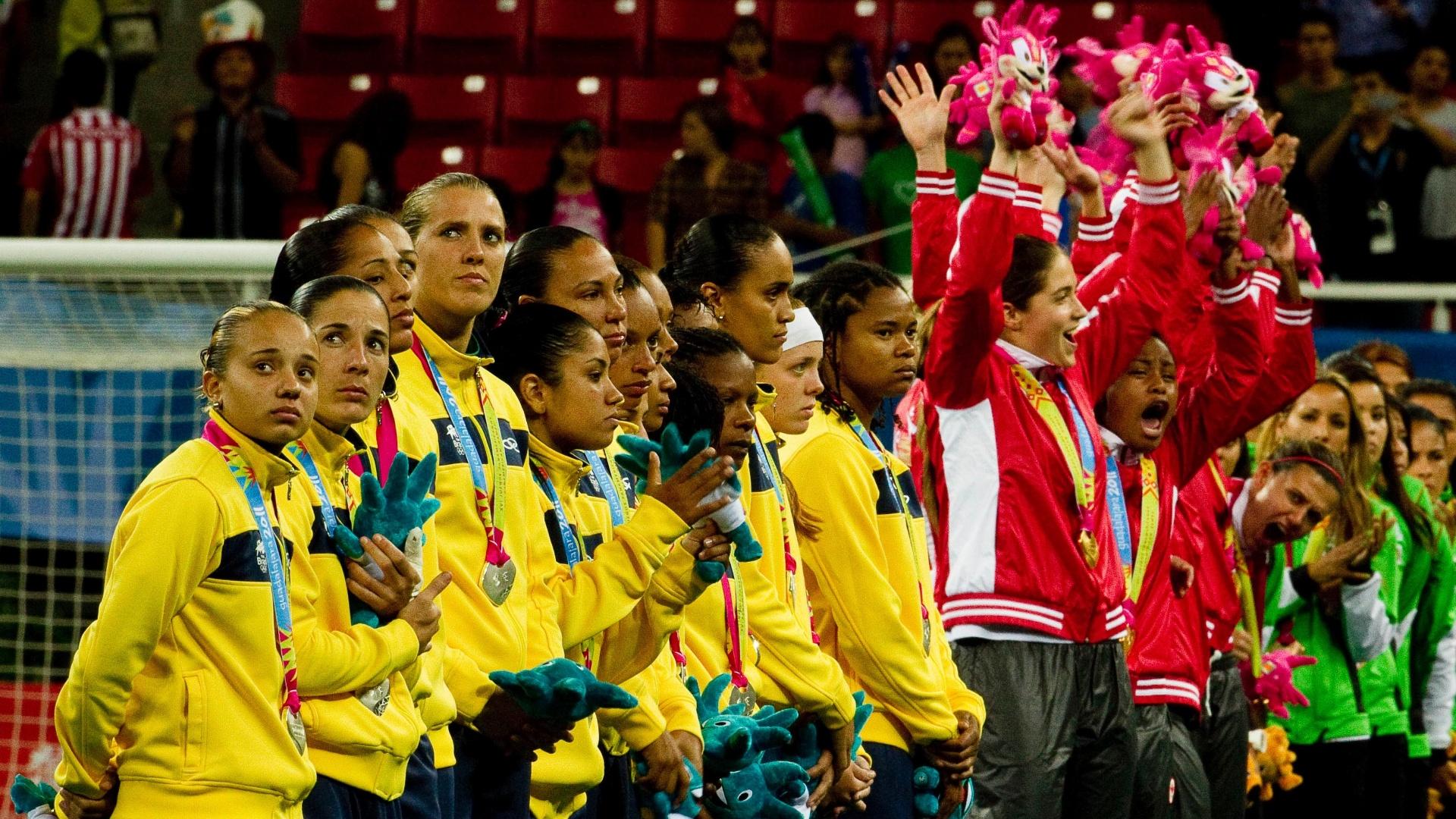 No pódio, brasileiras observam festa da seleção do Canadá após decisão no futebol feminino (27/10/2011)