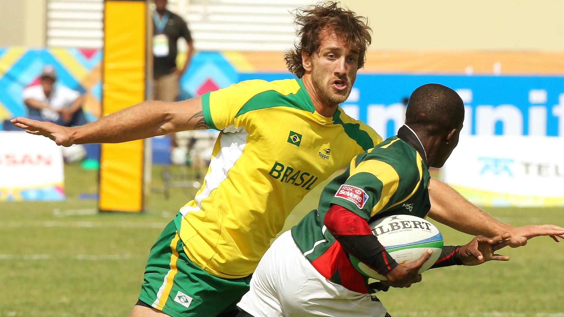 Brasileiro cerca jogador da Guiana no último jogo do rúgbi brasileiro no Pan; seleção ficou na sétima posição