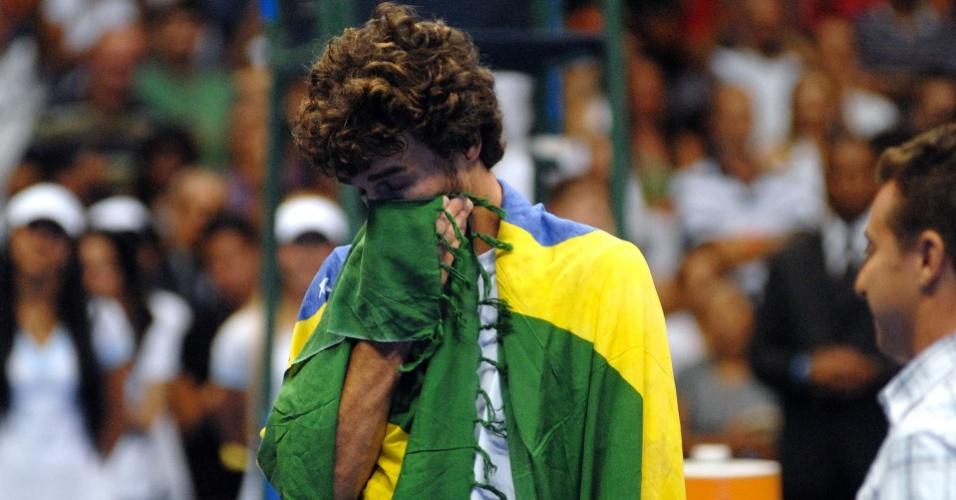 Enrolado na bandeira do Brasil, Guga chora ao ser homenageado depois de vencer Agassi em exibição no Rio de Janeiro
