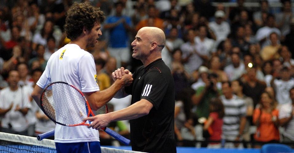 Guga abraça Agassi depois de vencer o rival em exibição no Rio