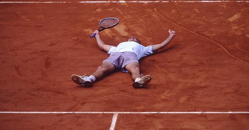 Gustavo Kuerten deita sobre coração no saibro de Roland Garros após o tricampeonato