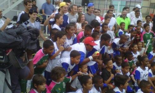 Gustavo Kuerten posa para foto com crianças da comunidade da Mangueira durante visita com espanhóis Alex Corretja e Carlos Moyá (17/11/2011)