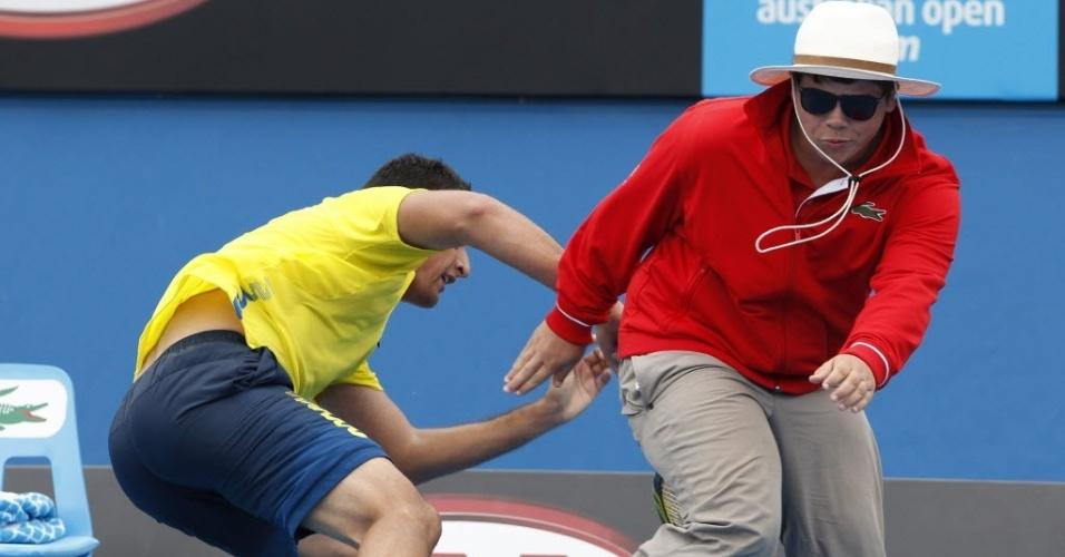 Tenista Nicolás Almagro parece buscar algo no traseiro do juiz de linha do Aberto da Austrália, que foge (20/01/2012)