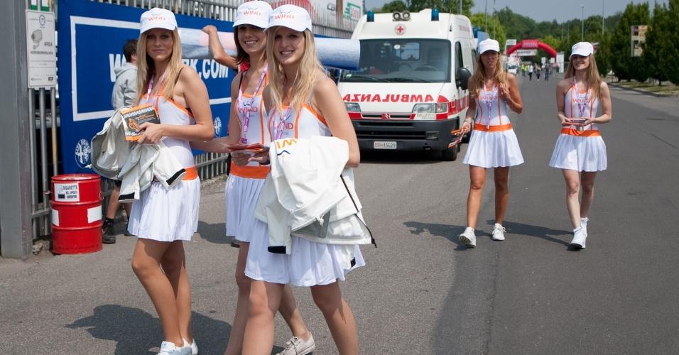 Grid girls caminham pelo paddock durante dia de treinos livres do Mundial de Superbike, em Monza, Itália. Ambulância já estava a postos ao fundo no caso de alguém passar mal