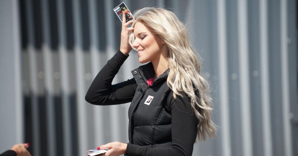 Grid girl sorri durante o treino classificatório da etapa de Silverstone de MotoGP