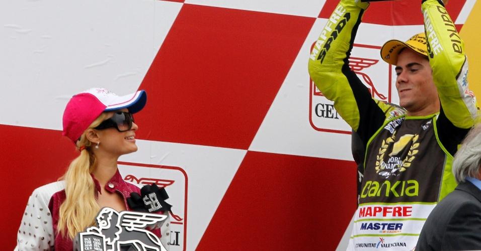 Paris Hilton segura troféu após vitória de sua equipe e observa o espanhol Nicolas Terol campeão da 125 cc em Valência (06/11/2011)