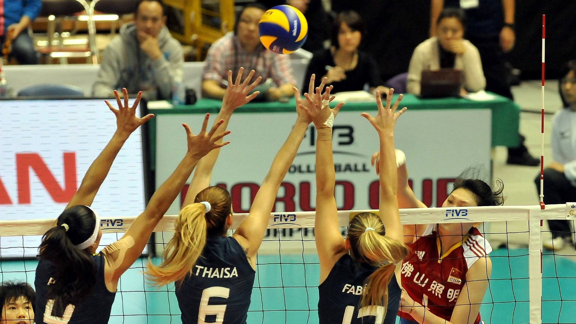 O triplo brasileiro, com Paula Pequeno, Thaisa e Fabíola, sobe para bloquear o ataque chinês (11/11/11)