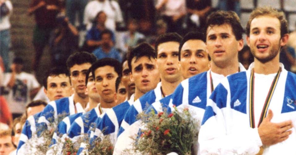 Jogadores da seleção brasileira de vôlei ouvem o Hino Nacional após a conquista do ouro olímpico em Barcelona-1992